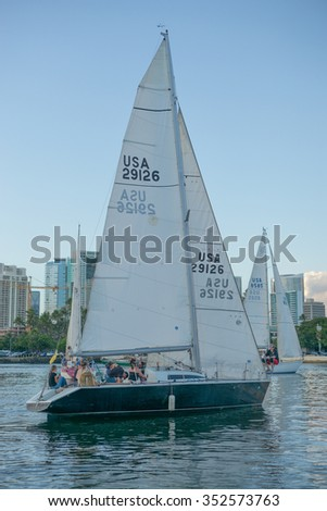 Honolulu, Hawaii, USA, Dec. 18, 2015:  Evening view of a sailboat crew maneuvering with skill in light winds.  Sailing is sport, transportation and lifestyle in the Hawaiian Islands.