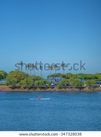 Honolulu, Hawaii, USA, Dec. 5, 2015:  Morning view of the Ala Wai Lagoon as a solo outrigger canoe paddler ventures out.  The Ala Wai Lagoon is part of the Ala Wai Harbor and the gateway to Waikiki.