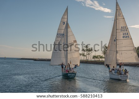 Honolulu, Hawaii, USA, Feb.  26, 2017:  Evening panorama view of two sailboats leaving the Ala Wai Harbor sailing wing on wing.