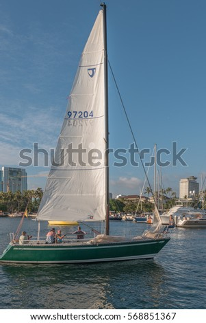 Honolulu, Hawaii, USA, Feb. 1, 2017:  Profile view of a green sailboat on an evening sail around Waikiki with Ala MOana Shopping Center in the backdrop.