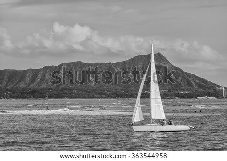 Honolulu, Hawaii, USA, Jan. 17, 2016:  A racing sailboat sails into the Ala Wai Channel after a race in Waikiki with Diamond Head Crater in the background.  Sailing is a year round activity in Hawaii.