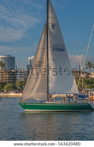 Honolulu, Hawaii, USA, Jan. 24, 2017:  Winter evening view of a sleek green sailboat leaving for a sail around Waikiki.
