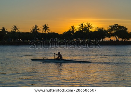 Honolulu, Hawaii, USA, June 11, 2015:  A rare green flash sunset in Honolulu Hawaii as a outrigger canoe paddlers heads out to Waikiki.  Waikiki is a world class center for ocean recreation.