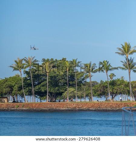 Honolulu, Hawaii, USA, May 20, 2015:  An Osprey Aircraft flies past Magic Island at Ala Moana Beach Park in Honolulu, Hawaii.  The Osprey takes off vertically and flies as a conventional aircraft. - stock photo