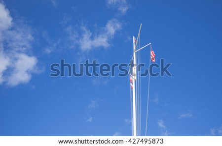 Honolulu, Hawaii, USA, May 27, 2016:  Morning view of a flagstaff with flags against a partly cloudy sky backdrop.