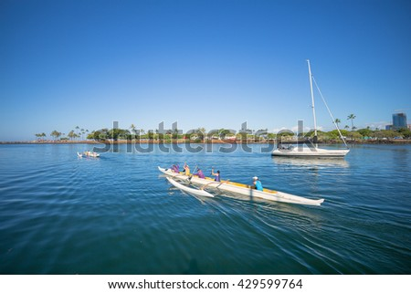 Honolulu, Hawaii, USA, May 31, 2016:  Morning view of  outrigger canoes and a sailboat in the Ala Wai Harbor with Ala Moana Beach Park in the background.