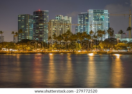Honolulu, Hawaii, USA, May 21, 2015: The Honolulu cityscape on a windy night.  Numerous construction cranes point to additional high rise condominiums in the future for Honolulu residents. - stock photo