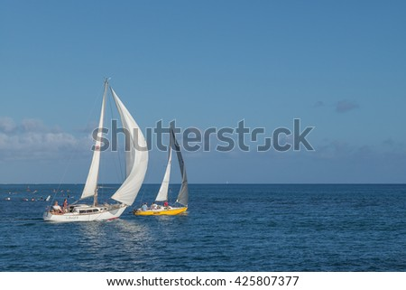 Honolulu, Hawaii, USA, May 24, 2016:  Two sailboats race out to sea from Waikiki on a journey to the outer islands with waiting surfers in the background.