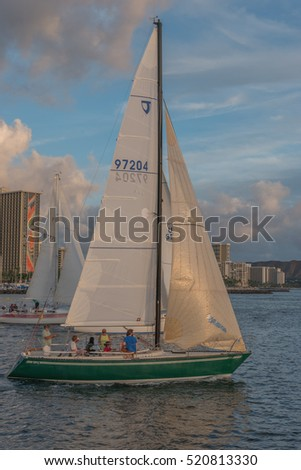 Honolulu, Hawaii, USA, Nov. 23, 2016:  Closeup view of a sailboat and crew as they head out to sea with hotels in the background.