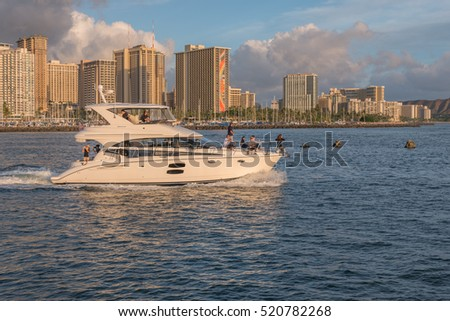 Honolulu, Hawaii, USA, Nov. 23, 2016:  Luxury powerboat and passengers head out to see with Waikiki hotels in the background.
