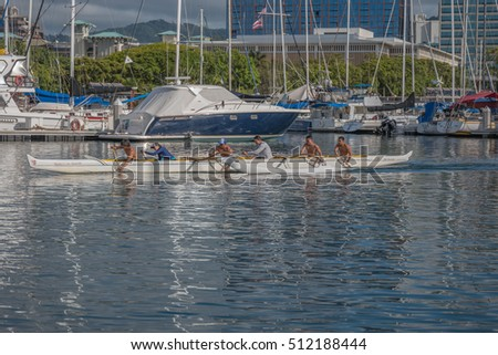 Honolulu, Hawaii, USA, Nov. 8, 2016:  Smiling outrigger canoe team paddling out to Waikiki with Ala Moana Shopping Center in the backdrop.