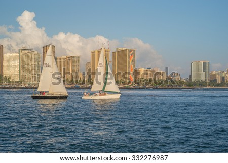 Honolulu, Hawaii, USA, Oct. 27, 2015: Afternoon sunlight on the Hilton Rainbow Tower and Waikiki Resorts as two sailboats race out to sea in the foreground.  Waikiki is a sailing center in Hawaii.