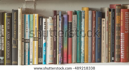 Honolulu, Hawaii, USA, Sept. 26, 2016:  Colorful panorama of old books with a white shelf backdrop.