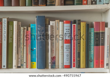Honolulu, Hawaii, USA, Sept. 30, 2016:  Selected books on a white book shelf with varied subject matter.