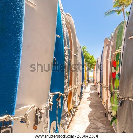 HONOLULU, HI, USA - September 7, 2013: Surfboards lined up in the rack at famous Waikiki Beach in Honolulu. Oahu, Hawaii. Waikiki white sand beach shoreline is Hawaii's most famous beach. - stock photo