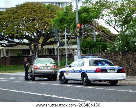 HONOLULU - MAY 3:  Honolulu Police Department police officer pulls over SUV car on Vineyard street. The HPD officer is talking to person in car, Hawaii July 4, 2012. - stock photo