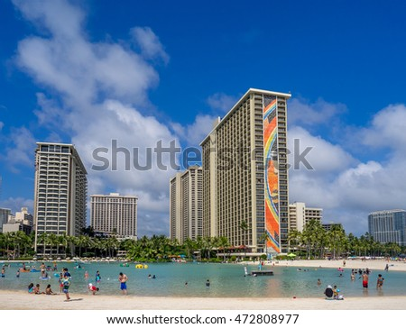 HONOLULU, USA - AUG 7: Sun lovers on Waikiki beach at the Hawaiian Hilton on August 7, 2016 in Honolulu, Usa. Waikiki beach is neighborhood of Honolulu, best known for white sand and surfing.