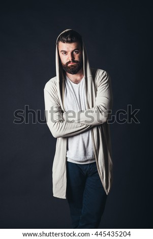 hooded and bearded men in studio, isolated black