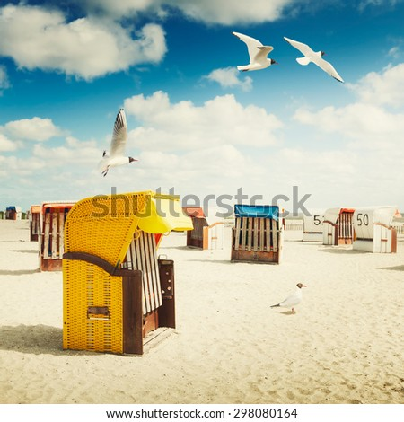 Hooded chairs on sand beach. Sea gulls flying in blue cloudy sky. Vacation background. North sea coast, travel destination. Toned in warm colors - stock photo