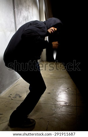 Hooded criminal with a knife hiding in the shadows of a street alley.  He is in a dark alley and partially visible as a silhouette.