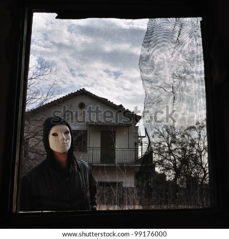 Hooded figure behind threaded window of derelict house. Masked maniac looking at you the viewer! - stock photo