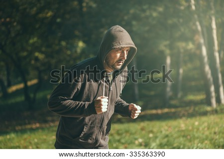 Hooded man jogging in the park in early autumn morning, sport, recreation and healthy lifestyle concept, retro toned image with selective focus - stock photo