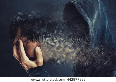Hooded man taking off his face mask, revealing spooky faceless person behind