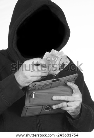 Hooded thief steals a wallet full of personal information and money - stock photo