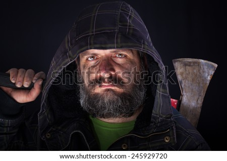Hooded tough guy with dirty face holding axe on shoulder - stock photo