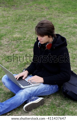 Hooded unisex student studying on computer while sitting in park on grass