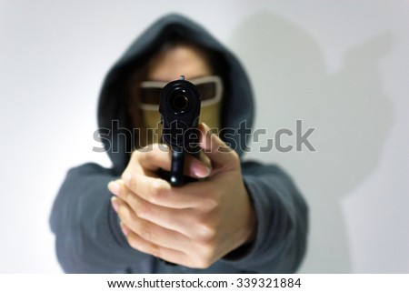 Hoodie woman with gun in studio - stock photo
