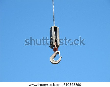 hook of a crane hanging from a cable with the sky as background - stock photo