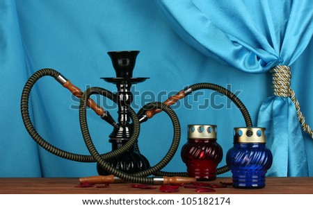 hookah on a wooden table on a background of blue curtain close-up - stock photo