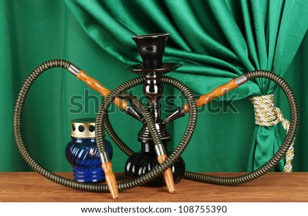 hookah on a wooden table on a background of green curtain close-up - stock photo