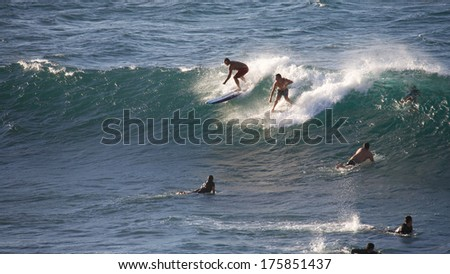 HOOKIPA, HAWAII - CIRCA OCTOBER 2013: Young people surfing Hookipa, Maui. Hookipa is a beach on the north shore of Maui, Hawaii, USA, perhaps the most renowned windsurfing site in the world
