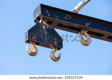 Hooks hanging on beam of harbor crane over blue sky background - stock photo