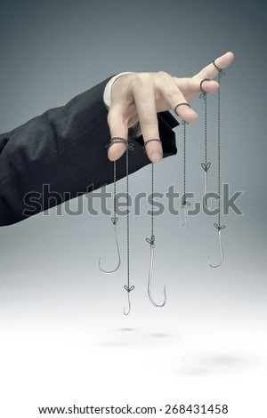 Hooks hanging on businessman hand - stock photo