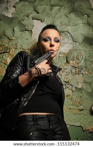 hooligan girl blowing on smoking gun - stock photo