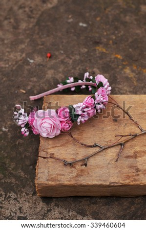 Hoop from flowers, wreath with colored flowers. Handmade flowers wreath on outdoor wooden stand.  Accessory. Artificial flowers. Hair accessories. Beauty. Fashion. Decoration for the head. Wreath hair - stock photo