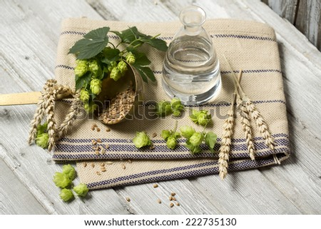 Hop flowers, wheat ears and seeds, water. ingredients for brewing beer on wooden table - stock photo