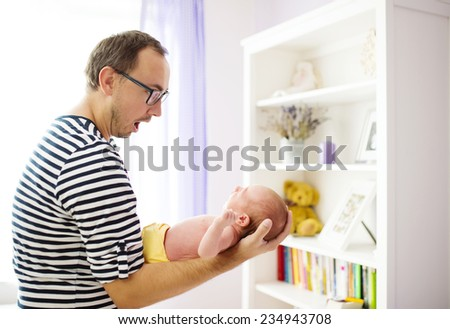 Hopeless daddy holding newborn daughter at home - stock photo