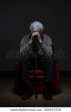 Hopeless disabled retiree sitting in an armchair - stock photo