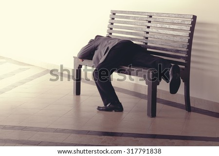 Hopeless stress businessman lay on bench with tired and loose from work - stock photo