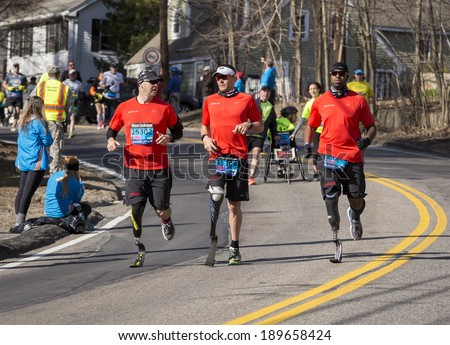 HOPKINTON, USA - APRIL 21: Athletes with disabilities heading fast from Hopkinton to Boston in Massachusetts, USA just a few minutes after the start of the Boston Marathon 2014 on April 21,2014.  - stock photo