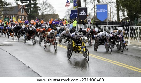 HOPKINTON, USA - APRIL 20: Male athletes with disabilities heading fast from Hopkinton to Boston a few seconds after the start of the Boston Marathon 2015 in Hopkinton, MA, USA on April 20, 2015.  - stock photo
