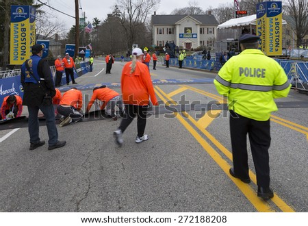 HOPKINTON, USA - APRIL 20: The start line of the Boston Marathon 2015 a few minutes before the start of the competition with staff members, locals, and police going about on April 20, 2015.