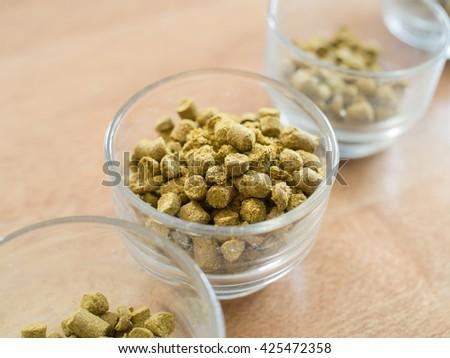 Hops pellets in glass cup for brewing beer - Beer ingredient - stock photo