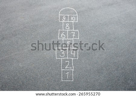 Hopscotch game being drawn with a chalk on the asphalt ground as seen from above - stock photo