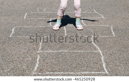 Hopscotch play. Girl hopping on a hopscotch game painted on pavement.