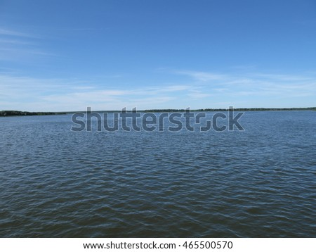 Horizon line in the lake and blue sky in a summer day